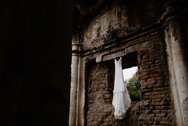 Wedding dress hanging on some ruins