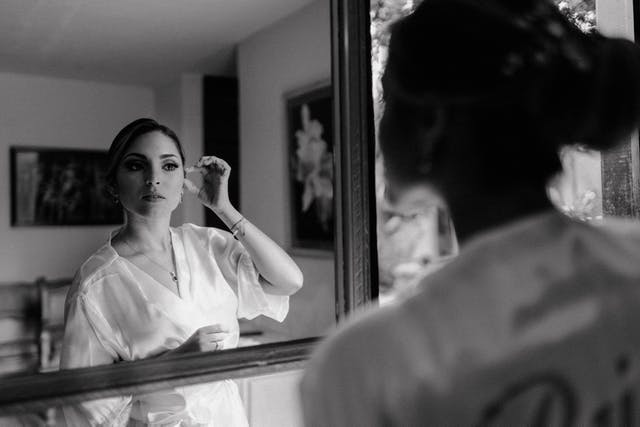 Bride watching her hairstyle and makeup for her wedding in the mirror