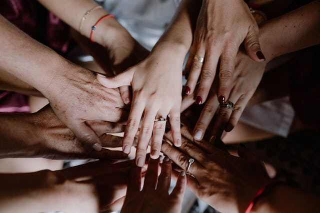 The hands of the bride and her godmothers together to encourage her