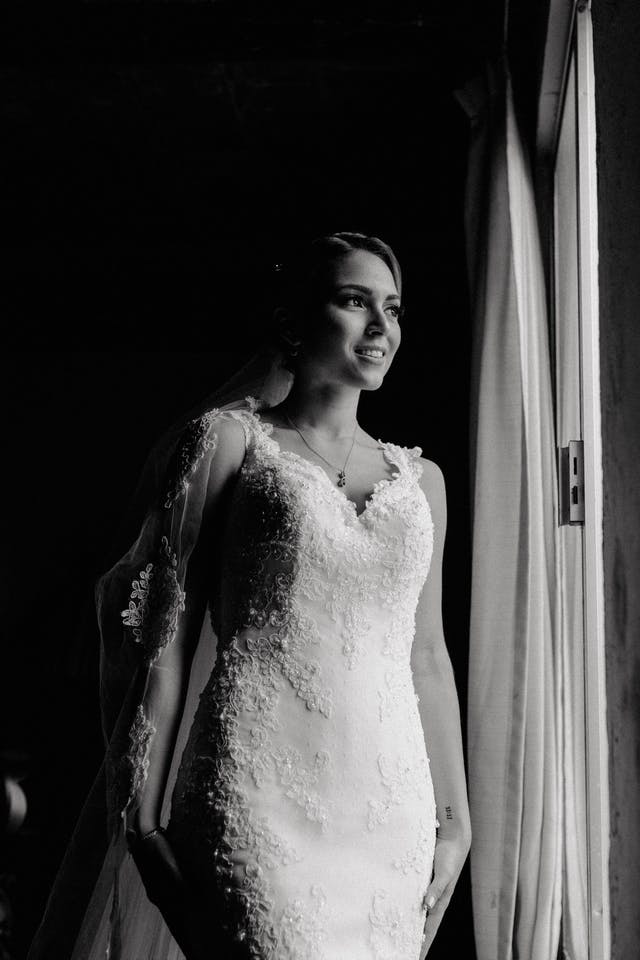The bride peeking out the window of her room on her wedding day