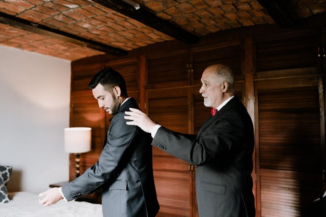 Father helping his son to dress for his wedding