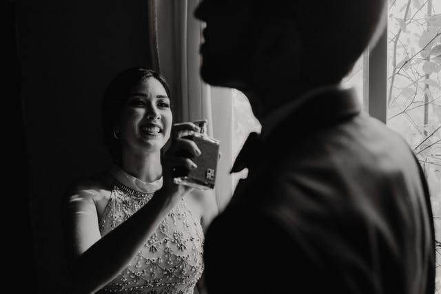 Sister of the groom smiling and putting perfume on her