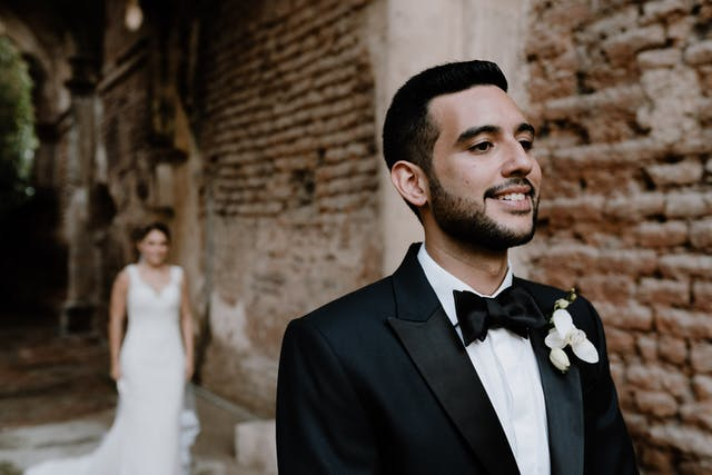 Boyfriend smiling before seeing his fiancee for the first look