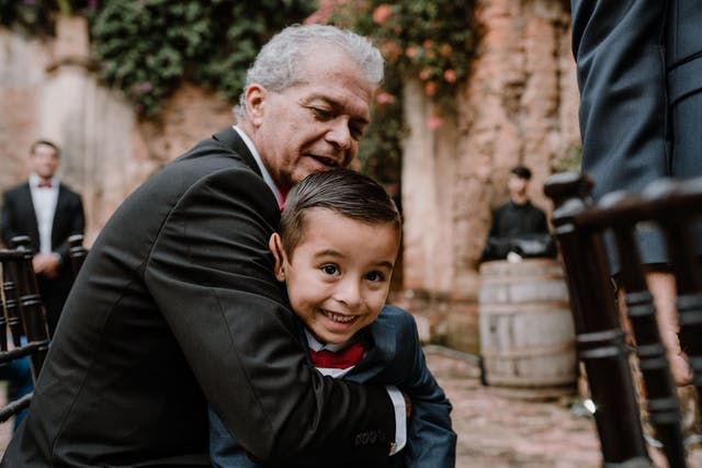 Grandfather hugging his grandson at the wedding