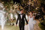 Groom and bride entering their wedding with fireworks